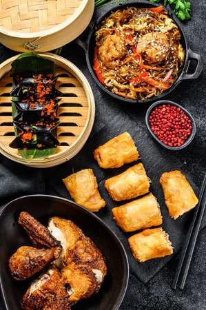 Chinese food. Noodles, dumplings, stir fry chicken, dim sum, spring rolls. Chinese cuisine set. Black background. Top view Reklamní fotografie