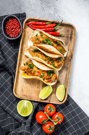 Tacos with crispy chicken, parsley, cheese and chili peppers. White background. Top view