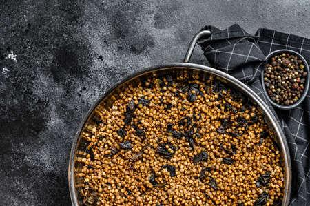 Buckwheat porridge with mushrooms. Vegan food. Russian, Ukranian cuisine. Black background. Top view. Copy space Reklamní fotografie