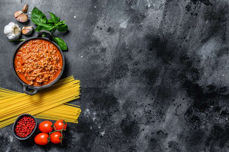 The concept of cooking Pasta spaghetti with tomatoes, sauce bolognese, cheese and basil. Black background. Top view. Copy space Reklamní fotografie