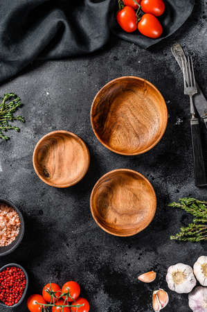 Black empty wooden plates in center of Fresh raw greens, vegetables. Healthy, clean eating, vegan, dieting food concept. Black background. Top view. Copy space Reklamní fotografie