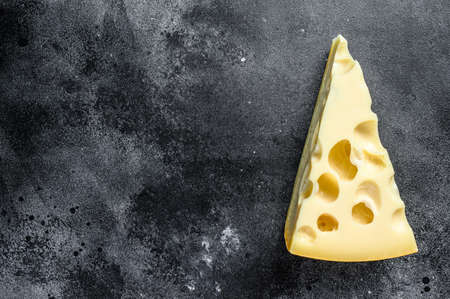 Piece of Maasdam cheese with large holes. Black background. Top view. Copy space Reklamní fotografie