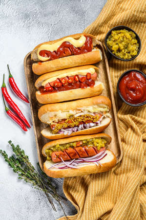 Hot dogs fully loaded with assorted toppings on a tray. Delicious hot-dogs with pork and beef sausages. White background. Top view