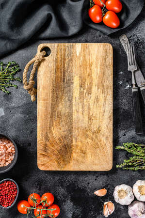 Wooden cutting board in center of Fresh raw greens, vegetables. Healthy, clean eating, vegan, dieting food concept. Black background. Top view. Copy space Reklamní fotografie