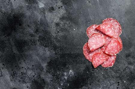 Slices of spanish salami salchichon. Black background. Top view. Copy space