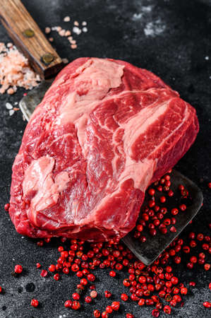 Fresh raw beef marbled steak. Chuck eye roll on a cleaver. Black background. Top view.
