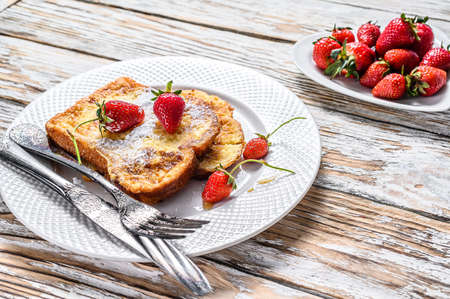 Two fried French toast with powdered sugar and strawberries. White background. Top view.