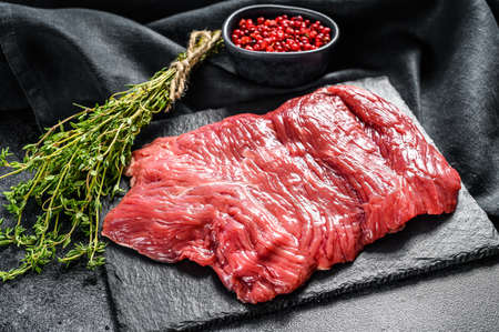 Raw outside skirt steak, marbled meat. Black background. Top view.