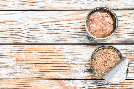 Canned tuna in a jar. Gray wooden background. Top view. Copy space.