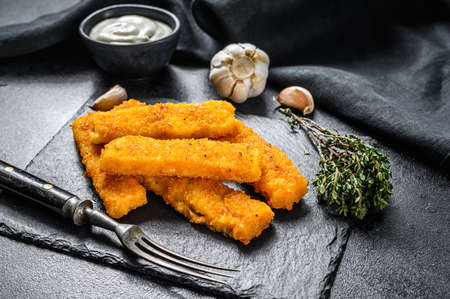 Crispy fried fish fingers with breadcrumbs served with sauce tartar. Black background. Top view.