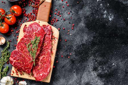 Marble beef Denver steak on a cutting board. Organic meat. Black background. Top view. Copy space. Zdjęcie Seryjne