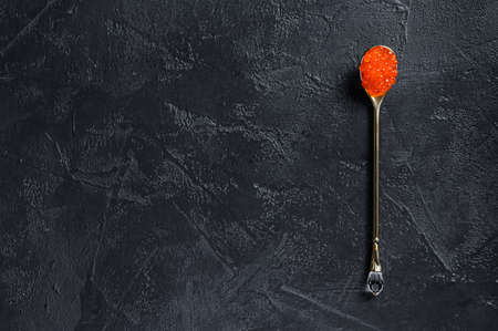 Red caviar in an exquisite spoon. Black background. Top view. Copy space.