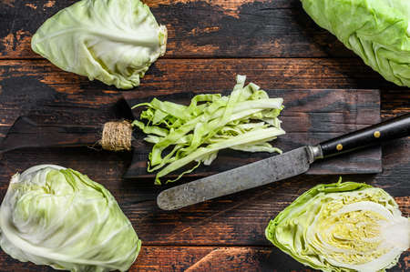 Fresh sliced Green pointed cabbage. Wooden background. Top view.