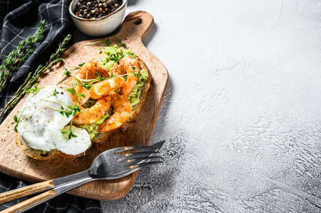 Toast with shrimp, prawns, avocado and poached egg. Gray background. Top view. Copy space.