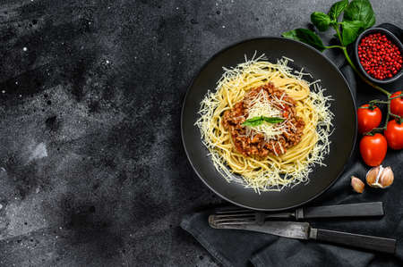 Spaghetti bolognese pasta with tomato and minced meat, parmesan cheese and basil. Black background. Top view. Copy space.