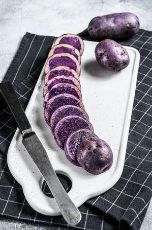 Raw sliced purple potatoes on a white chopping Board. Gray background. Top view. 版權商用圖片