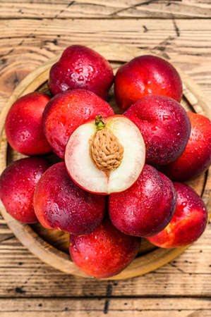 Tray of Fresh red nectarines. Wooden background. Top view. Фото со стока