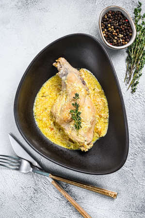Braised rabbit legs with rosemary and garlic. Gray background. Top view.