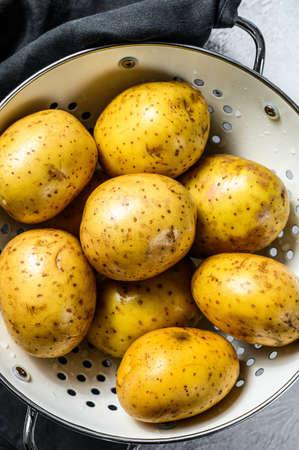 Organic yellow potatoes in a colander. Gray background. Top view. 版權商用圖片