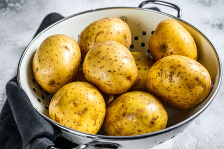 Raw washed potatoes in a colander. Gray background. Top view.