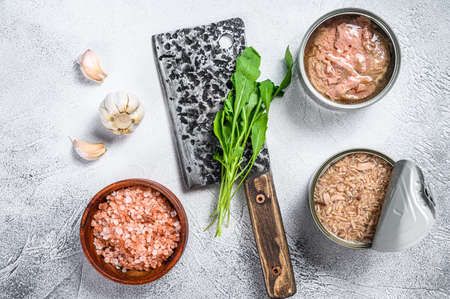 Canned tuna in a can, whole and chopped. Gray wooden background. Top view.