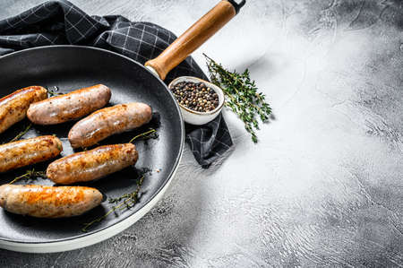 Tasty homemade sausages in a pan. Pork, beef and chicken meat. Gray background. Top view. Copy space.