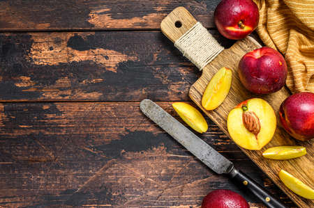 Sliced ripe red nectarines on a chopping Board. Dark Wooden background. Top view. Copy space.