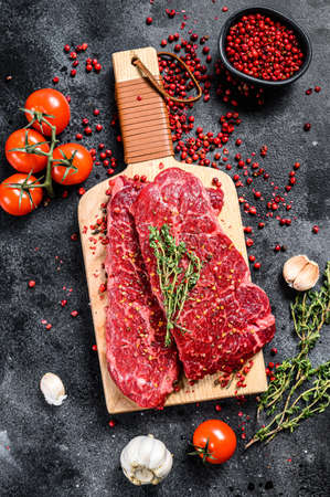 Marble beef Denver steak on a cutting board. Organic meat. Black background. Top view.