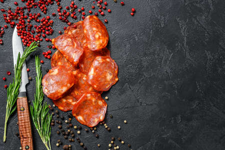 Spanish sliced chorizo sausage. cured meat. Black background. Top view. Copy space.