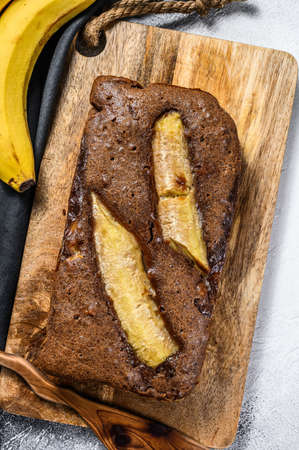 Freshly baked delicious banana bread with walnuts and chocolate. Gray background. Top view.