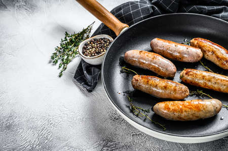 Grilled assorted pork, beef and chicken sausages with spices in a pan. Gray background. Top view. Copy space.