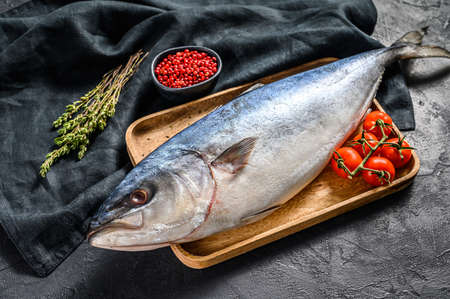 Fresh whole raw Japanese yellowtail with tomato and herbs. Fish Amberjack. Black background. Top view. Copy space.