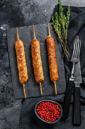 Homemade pork meat kebabs on skewers. Black background. Top view.