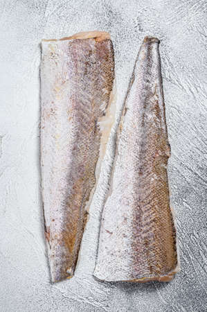 Raw fillet of hake fish. White background. Top view.