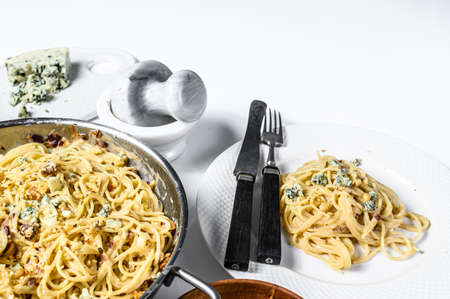 Spaghetti pasta with blue Gorgonzola cheese sauce. White background. Top view. Copy space.