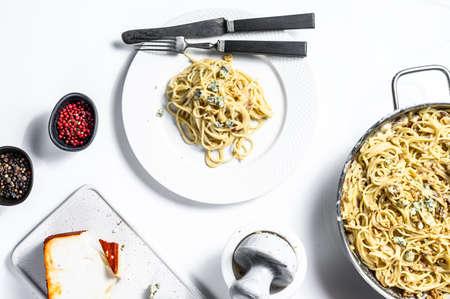 Spaghetti pasta with blue Gorgonzola cheese sauce. White background. Top view.