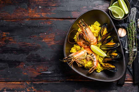 The Spanish Seafood paella with prawns, shrimps, octopus and mussels. Black wooden background. Top view. Copy space.