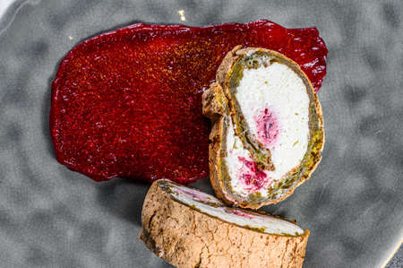 Slice of Swiss roll with strawberry jam and cream. Black background. Top view.
