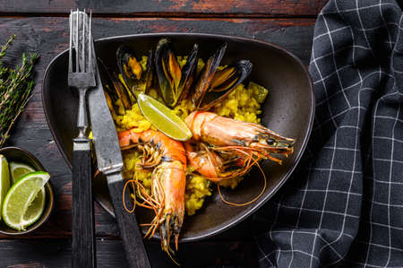 The Spanish Seafood paella with prawns, shrimps, octopus and mussels. Black wooden background. Top view.