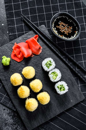 Various kinds of sushi served on black stone. Black background. Top view.