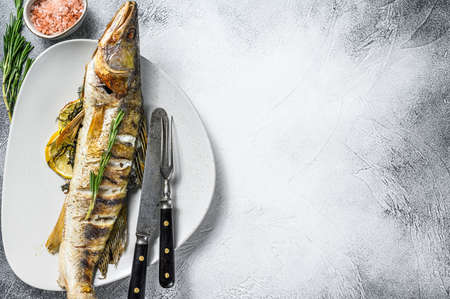 Grilled Zander, walleye fish with herbs and lemon on a plate. Gray wooden background. Top view. Copy space. Archivio Fotografico