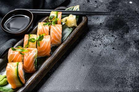 Philadelphia maki sushi with salmon, prawn, avocado, cream cheese. Sushi roll menu. Black background. Top view. Copy space. Imagens
