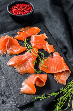 Salted salmon slices with pepper and thyme. Organic fish. Black background. Top view.