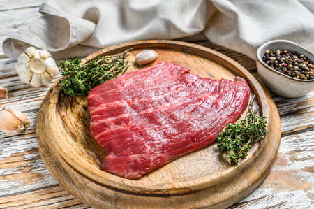 Raw Flat Iron steak on a cutting board. Fresh Marble beef meat black Angus. White wooden background. Top view. Archivio Fotografico