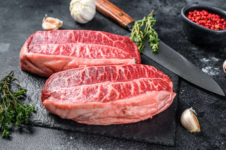 Raw top blade steak dry-aged on a stone board. Black background. Top view Banco de Imagens