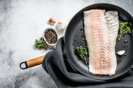 Raw cod fillet with thyme and herbs in a pan. Cooking fresh fish. Gray background. Top view. Copy space. Archivio Fotografico
