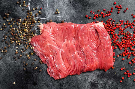 Raw outside skirt steak with black and pink pepper. Black background. Top view.