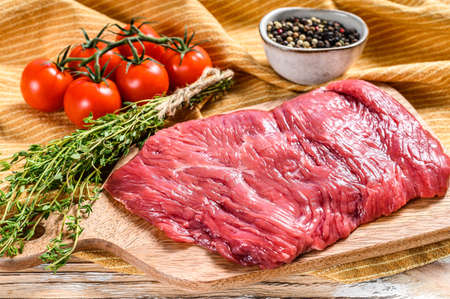Fresh flank steak on a chopping Board. White background. Top view.
