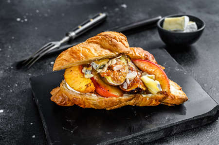 French croissant with bree cheese, peach and figs. Black wooden background. Top view.