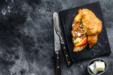 French croissant with bree cheese, peach and figs. Black wooden background. Top view. Copy space. Reklamní fotografie